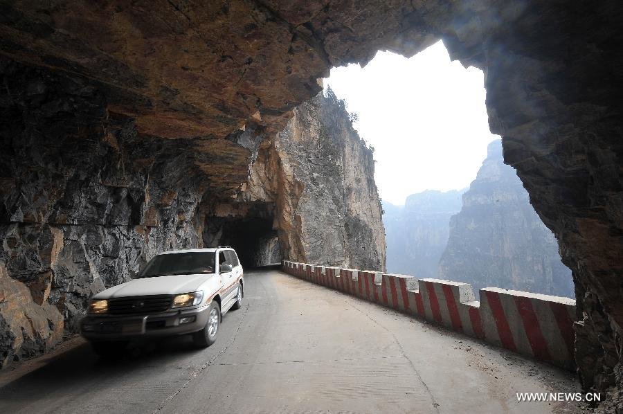 A car runs on the 'heavenly road' along the waist of the Taihang Mountains in Pingshun County, north China's Shanxi Province. The 1,526-meter-long road, which spirals up along the 1,100-meter-high Taihang Mountains is a shortcut to the Jingdi Village at the mountain foot. Local villagers spent 15 years to build the road and they call it 'heavenly road.' [Xinhua]