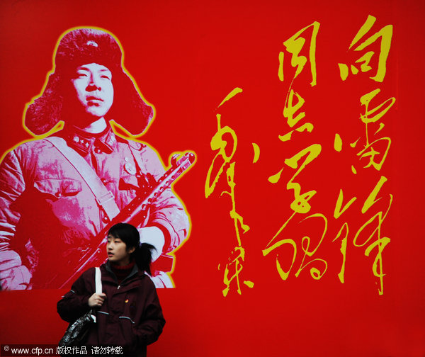 A woman passes a wall with a portrait of Lei Feng near a bookstore in Shanghai, March 3, 2012. [Photo/CFP]