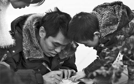 A boy guiding his father as he fills in an application form for a job at a Chinese company's overseas project while the boy's mother looks on. Many of these projects are in Africa and other developing economies, where, because of a shortage of material goods, there isn't much to spend money on so many send much of their earnings back home. [China Daily]