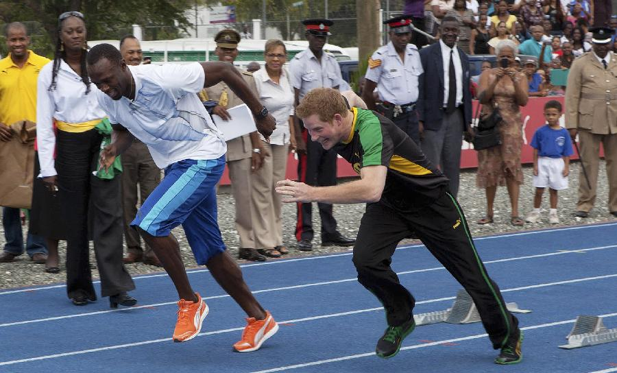 Britain's Prince Harry and Usain Bolt, Jamaica's champion sprinter, come out of the starting blocks on the track at the University of the West Indies in Kingston, Jamaica. (Xinhua/Reuters Photo)