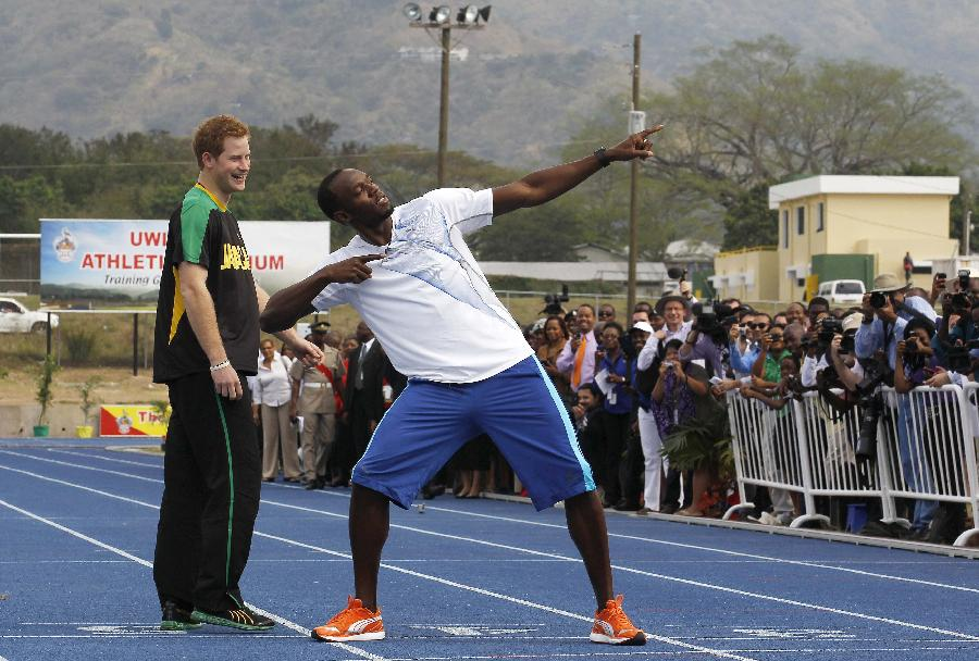 Britain's Prince Harry (L) looks on as Olympic gold medallist Usain Bolt poses at the Usain Bolt track at the University of the West Indies in Kingston, Jamaica March 6, 2012.