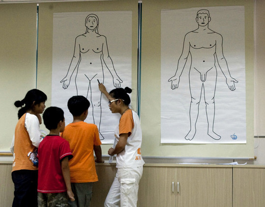 Gao Weiwei (right), a lecturer, talks to students about the human body at a summer camp focusing on sex education. The camp, believed to be the first of its kind in Shanghai, was established in 2009. [China Daily]