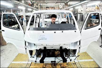 A Chinese carmaker's employees work at a factory in Shenyang, Liaoning Province, yesterday. Passenger car sales in China fell 1.4 percent in the first two months of this year. [Shanghai Daily]