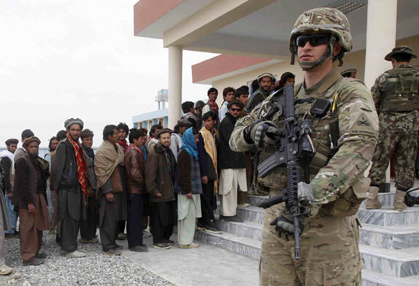 A US soldier stands guard as former Taliban members hand over their weapons as part of the Afghan government's reconciliation program in Laghman province on Monday. Tension in the country has risen sharply after the Taliban vowed revenge on Monday for an 'inhumane attack' in which an American soldier allegedly killed 16 villagers in Kandahar province. [Photo by Parwiz / Reuters]
