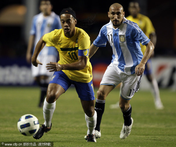 Argentina's Pablo Guinazu (left) chases Brazil's Ronaldinho during a soccer friendly match in Belem, Brazil on Wednesday, Sept. 28, 2011.