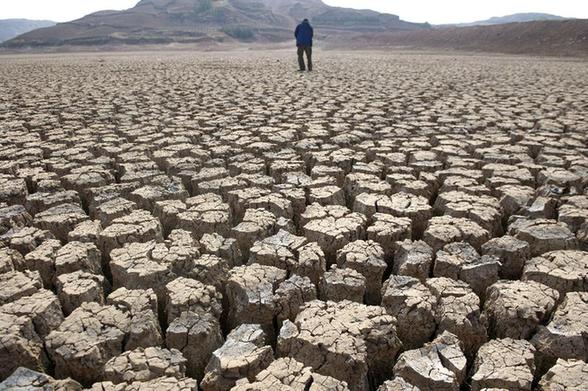 A villager walks on the dried-up bed of the Xinba reservoir in Shilin County, China's Yunnan Province, March 22, 2012. A severe drought has lingered in Yunnan for three consecutive years. [Xinhua]