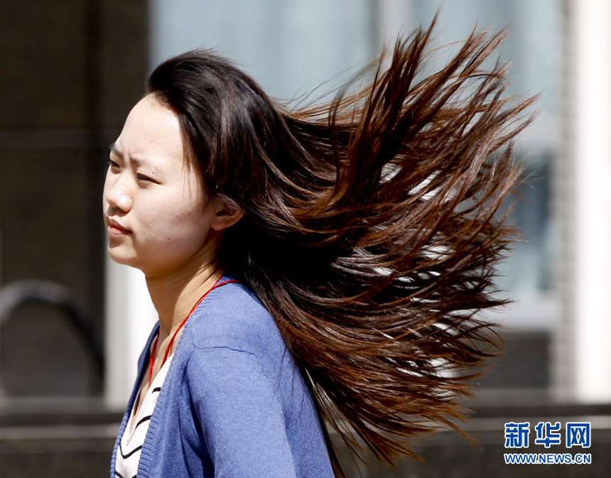 A girl walks against the gale in downtown Beijing, April 5. Meteorologists issue a strong wind warning early today.