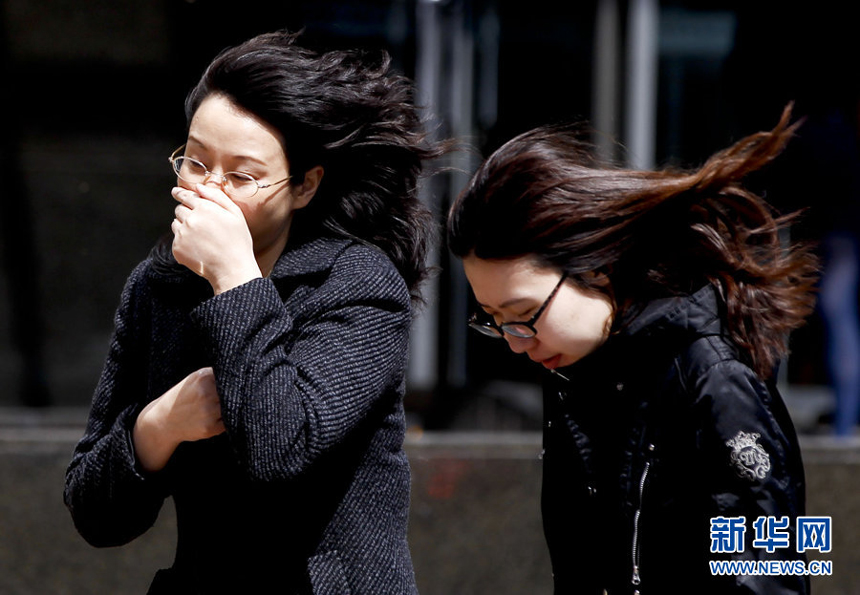 Two women walk against the gale in downtown Beijing, April 5. Meteorologists issue a strong wind warning early today.