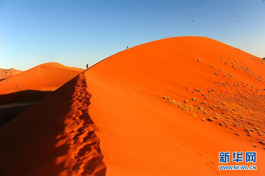 Tourists walk on the red sand dune in Sossusvlei desert park, Namibia, April 9, 2012. (Xinhua Photo)