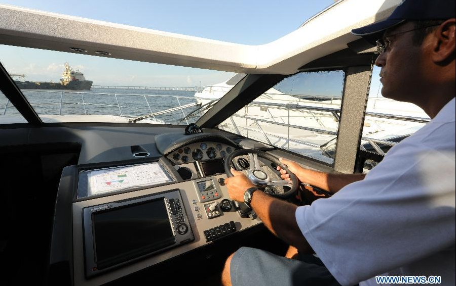 A man shows how to drive a model of yacht during the Rio Boat Show in Rio de Janeiro, Brazil, April 13, 2012. The Boat Show, biggest of its kind in Latin America, kicked off here Thursday. (Xinhua/Weng Xinyang) 