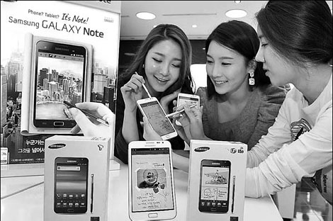 Models display the white model of Samsung's Galaxy Note smartphone during a publicity event in Seoul. Apple Inc says Samsung 'slavishly copies' its iPhone and iPad devices. [China Daily]
