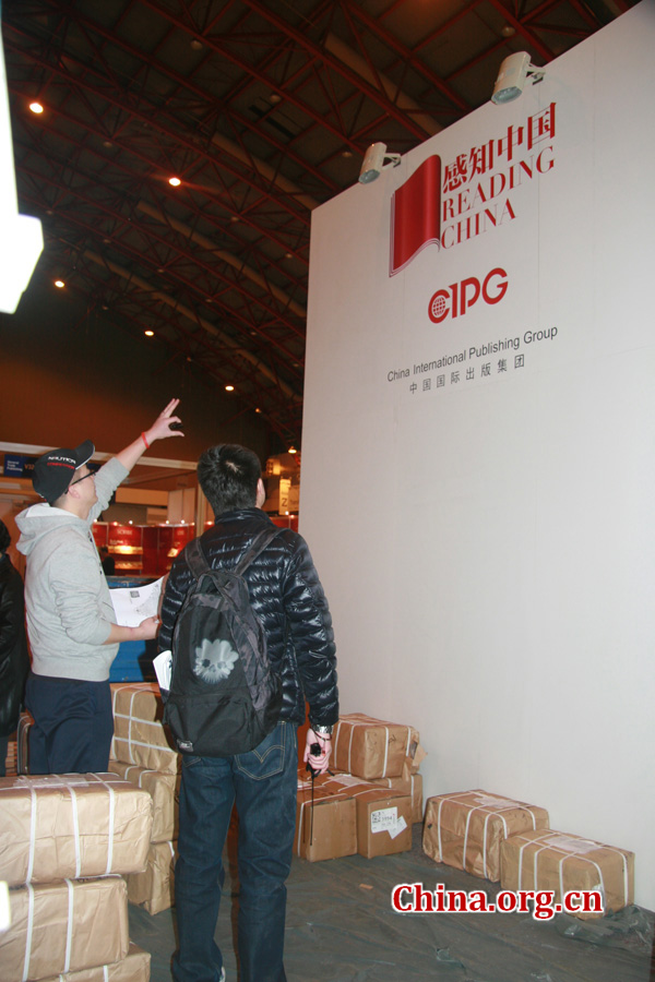 A CIPG employee and a decorator discuss the design of the CIPG booth during the London Book Fair.