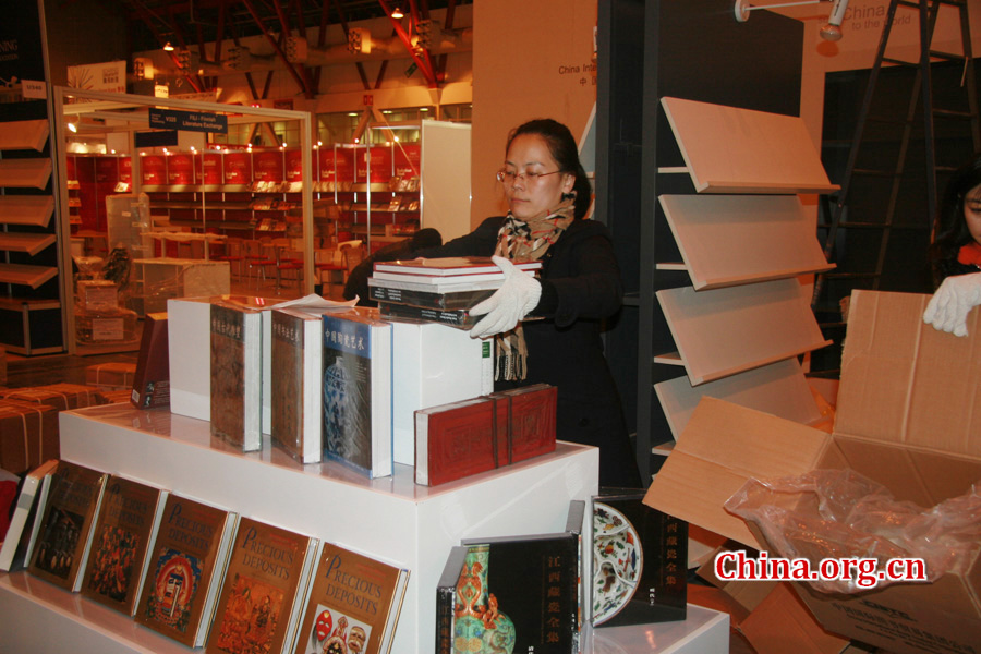 A CIPG employee arranges the books which will be displayed during the London Book Fair.