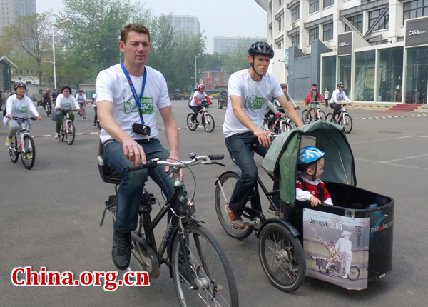 Some foreign participators ride bike with their baby in the front carrier.