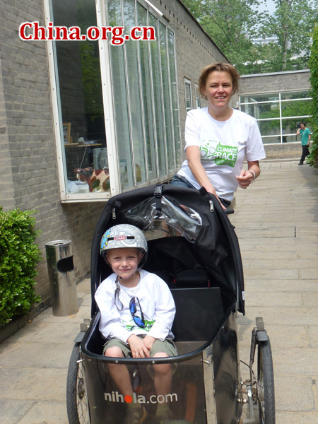 A foreign participant rides her bike with her son in the front carrier.