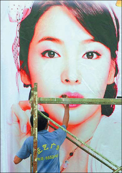 A worker preparing an outdoor advertising board in Nanjing, Jiangsu province. China's advertising market is growing rapidly, but the main players remain foreign firms. [File photo]