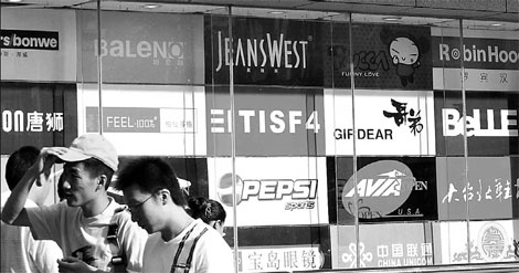 People walking past an advertising board of logos in Nanjing, Jiangsu province. Despite the de facto control of the market by foreign firms, local advertising companies have an edge in understanding local culture. [File photo]