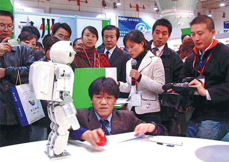 Visitors to a trade fair involving businesses from China, Japan and South Korea look at a robot in Qingdao, Shandong province. Experts say the time is ripe for the three countries to start talks on establishing a free trade area. [China Daily]