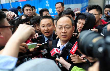 Jin Xiaoguang (center right) and Chen Gang (center left), lawyers for former Chinese Football Association deputy chief Xie Yalong are surrounded by reporters during a court recess yesterday in Dandong, Liaoning Province.