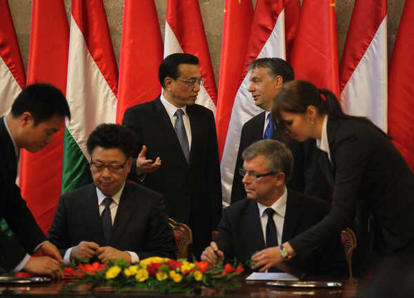 Vice-Premier Li Keqiang (back left) talks with Hungarian Prime Minister Viktor Orban during the signing of agreements at the parliament building in Budapest on Tuesday. [Fu Jing/China Daily]