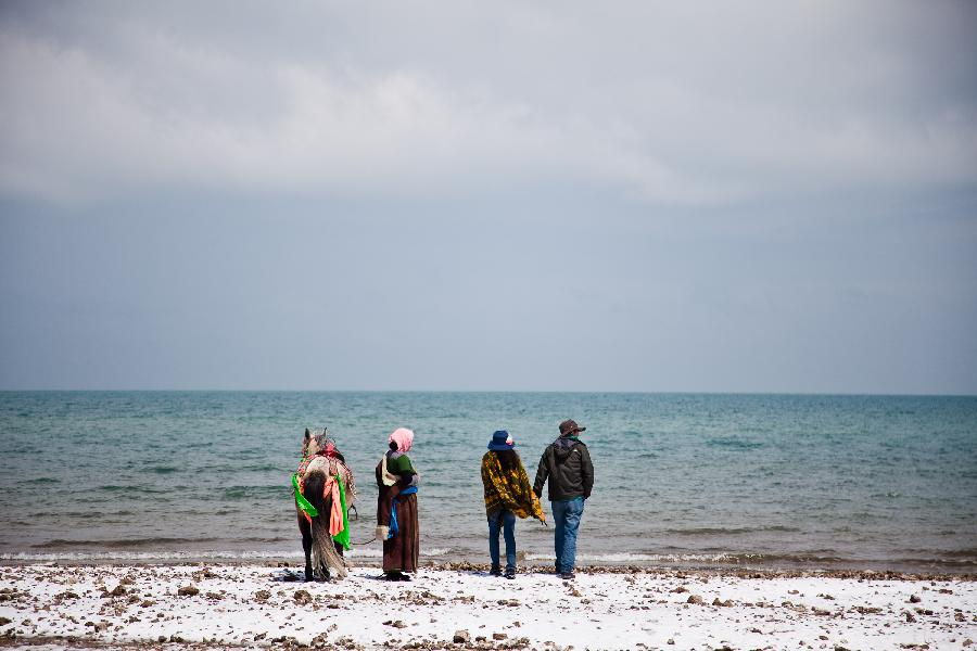 Tourists walk along the Qinghai Lake in northwest China's Qinghai Province, April 30, 2012. (Xinhua/Wu Gang)