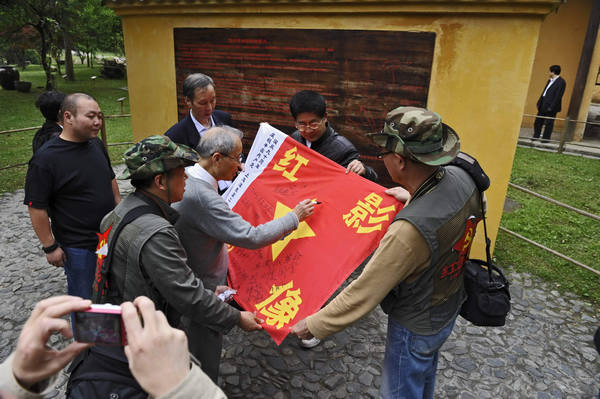 Visitors sign their names on a symbolic Red Army flag in Jinggangshan in the southwest of Jiangxi province. The admission price to the scenic spot will go up from 226 yuan per person to 260 yuan in May. Provided to China Daily