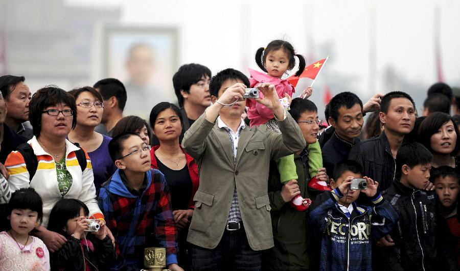 Tourists gather to watch the national flag-raising ceremony in Beijing, capital of China, May 1, 2012. As weather warms, a good many people choose to spend the three-day Labor Day holiday in travelling. (Xinhua/Lang Congliu)