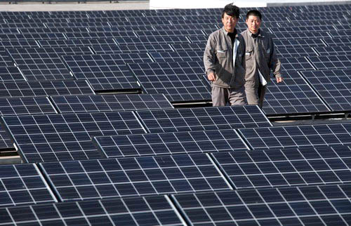 Workers check solar panels at a wastewater treatment facility in Tianjin Eco-City, a joint project between China and Singapore, on April 25. [China Daily]