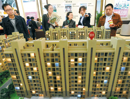 Visitors look at models of a housing project at the Nanjing (Spring) Real Estate Trade Fair on April 12. Average home prices in 100 Chinese cities fell 0.71 percent year-on-year in April, the first such drop since June 2011. [China Daily]