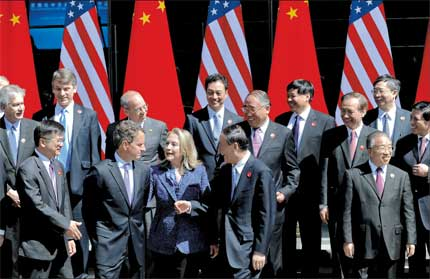 Chinese Vice Premier Wang Qishan (2nd right, 1st row), US Secretary of State Hillary Clinton (center) and Treasury Secretary Timothy Geithner (2nd left) and other officials share a light moment as they gather for a group photo at the Diaoyutai State Guesthouse in Beijing after the opening ceremony of the fourth China-US Strategic and Economic Dialogue yesterday. [Shanghai Daily]