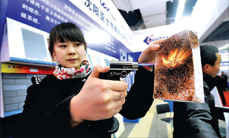 A woman demonstrating a heat-resistant material at a building materials fair in Shenyang, capital of Liaoning province. Many foreign companies are still bullish about China's property market and have continued to invest in both real estate and building materials.[China Daily]
