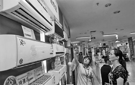 A sales clerk explaining the functions of air conditioners to a woman at an electrical appliances store in Nantong, Jiangsu province. China now has the largest heating ventilation air conditioner market in the world. It is also the largest manufacturer of such products.