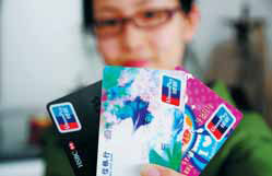A woman displays credit cards in Qingdao, Shandong province. Credit cards have become a driver of domestic consumption, being used in 7.56 trillion yuan ($1.2 trillion) of retail purchases last year. [China Daily]