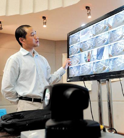 A faculty staff member tests the monitoring system at East China Model High School in Jing'an District yesterday to prepare for today's National College Entrance Exam, which will be attended by 9 million high school students across China. Strict measures have been taken to scuttle cheating on the big test.