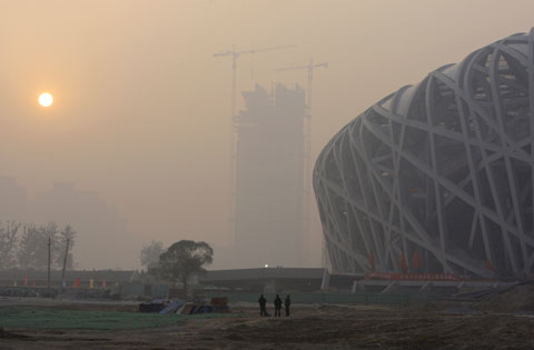Buildings are shrouded in haze and smog nearby Beijing National Stadium. [File photo]
