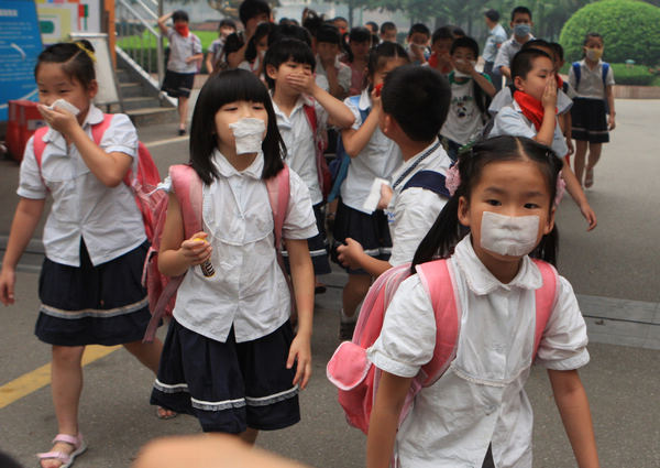 Students at the Yucai Primary School in Wuhan, capital of Hubei province, on Monday cover their mouths with pieces of cloth to prevent themselves from inhaling smog caused by straw burning. [ Photo / China Daily ]