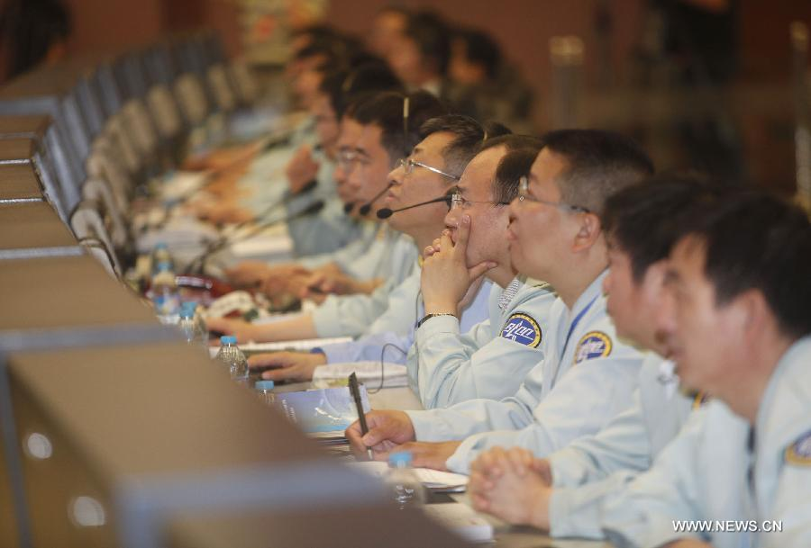 Staff members work during the launch of China's manned Shenzhou-9 spacecraft at the Beijing Aerospace Flight Control Center, in Beijing, capital of China, June 16, 2012. Shenzhou-9, atop an upgraded Long March-2F carrier rocket, blast off from the Jiuquan Satellite Launch Center in northwestern China at 6:37 p.m. Saturday and accurately entered its orbit. (Xinhua/Wang Shen)