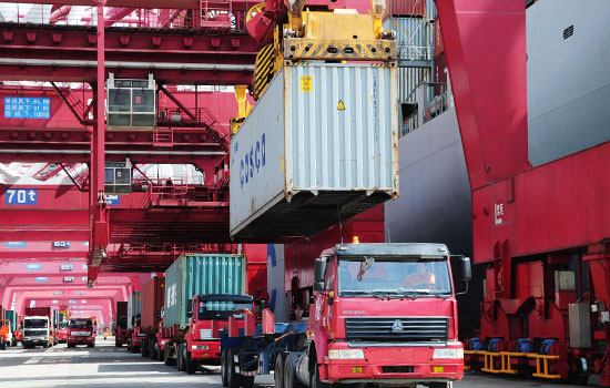 A container with export goods is offloaded from a truck at Qingdao port in Shandong province.