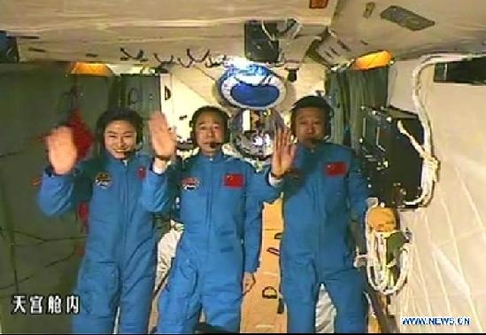 This screen shot taken on June 26, 2012 shows the Chinese astronauts who are conducting scientific tests in Tiangong 1 space lab module waving hands. Chinese President Hu Jintao came to the Beijing Aerospace Control Center on Tuesday and talked with the astronauts. [Xinhua]