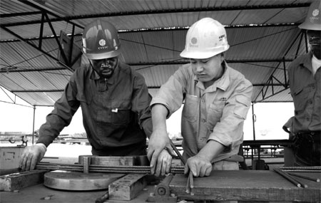 Chinese workers train their Angolan colleagues to roll steel at a CITIC Construction Co Ltd worksite in Luanda, the capital city of Angola.