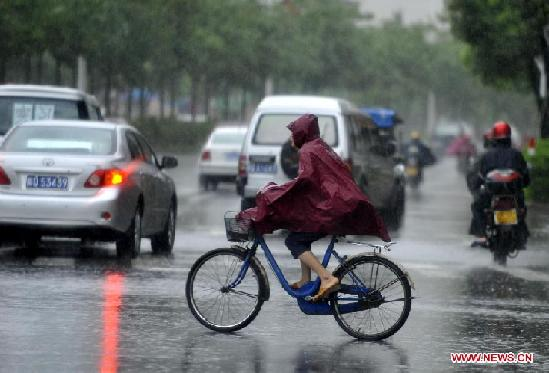 A citizen rides a bike while vehicles move against rainstorm on a street in Yangjiang, south China's Guangdong Province, July 24, 2012. Typhoon Vicente landed in Chixi Town of Taishan City in Guangdong early Tuesday.[ Photo / Xinhua ]