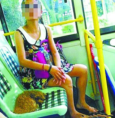 An unidentified female passenger lets her dog take a seat on a bus in Ningbo, Zhejiang province on July 25, 2012. [Photo: Yangtse Evening Newspaper]