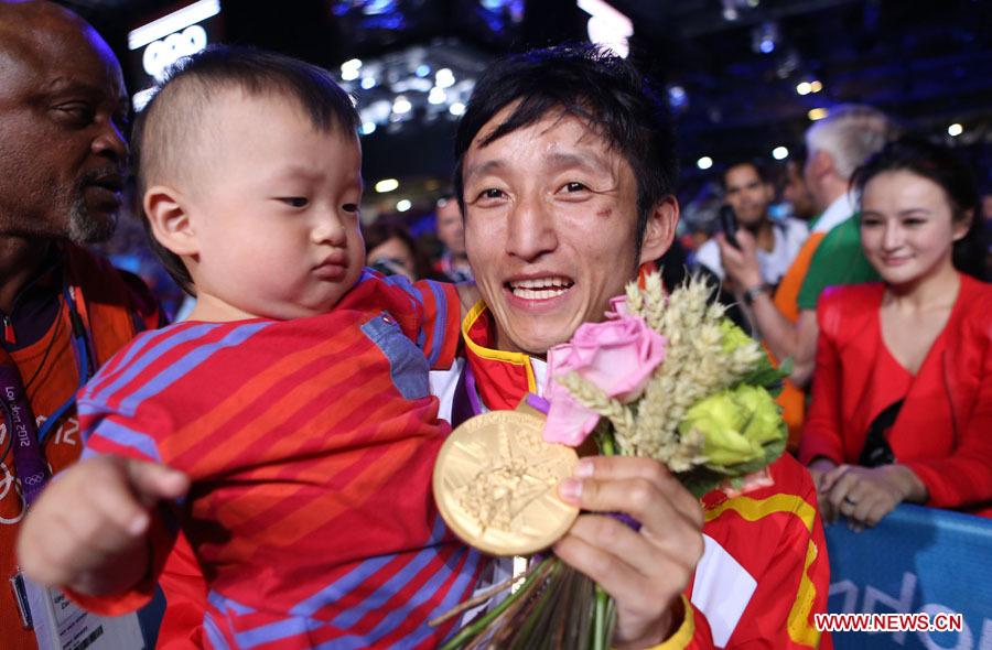 8月11日,邹市明的妻儿在赛场与他共同庆祝夺冠。当日,在伦敦奥运会男子拳击49公斤级决赛中,邹市明以13比10战胜泰国选手庞普里亚杨,获得冠军。[新华社/王申]