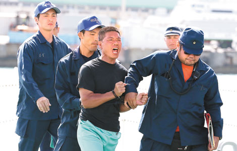 An activist who landed on the Diaoyu Islands is taken into police custody in Naha, the capital of Okinawa, on Thursday. [Agencies]