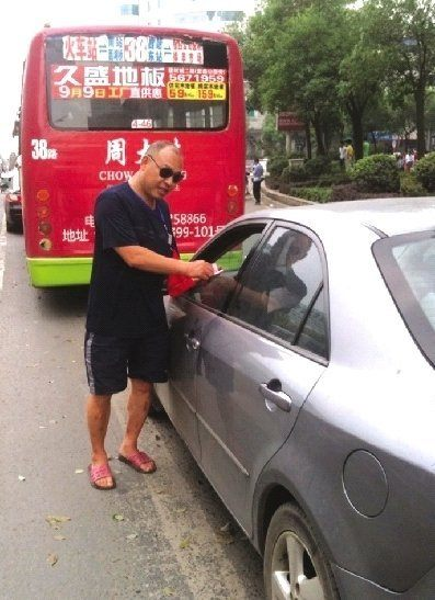A driver surnamed Zhang said 'someone suddenly knocked his window' when he was waiting for the lights to turn green demanding payment. He had stopped for the red light but had encroached on the crosswalk.[ Photo / dayoo.com]