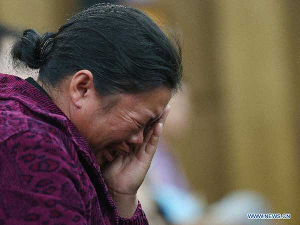 A relative of murdered Chinese sailor weeps tears at the Intermediate People's Court of Kunming, capital of Yunnan Province, Sept. 21, 2012. Naw Kham, principal suspect for the murders of 13 Chinese sailors on the Mekong River last year, pleaded guilty Friday evening when he and five other people were standing trial in southwest China. [Wang Shen/Xinhua]