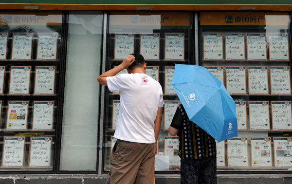 Two visitors look at house information at a real estate agency in the Chaoyang district of Beijing. Despite the month-on-month decline, September house sales have been stronger than a year ago. [Photo / Xinhua]