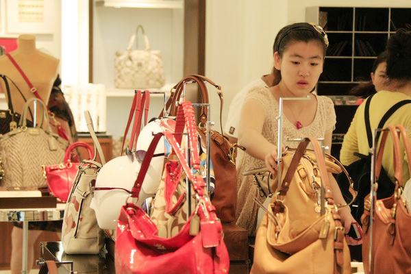 Shoppers select bags at a duty-free store in Sanya, Hainan province. Luxury, but without showing off, is what Chinese consumers look for now. [Huang Yiming / China Daily]