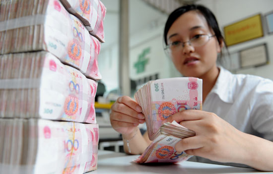 A bank employee counts money at a branch in Lianyungang, Jiangsu province. [Photo/China Daily]