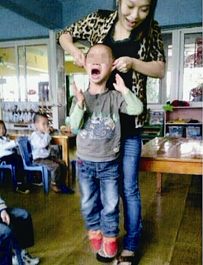 A female kindergarten teacher surnamed Yan in east China's Zhejiang Province holds up a boy by his ears.